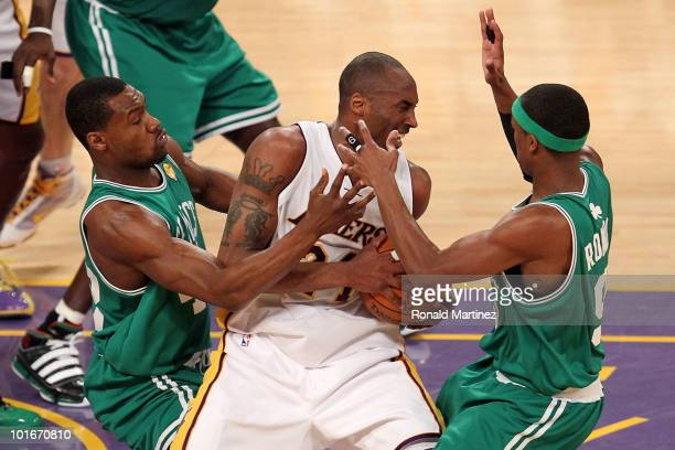 Kobe Bryant of the Los Angeles Lakers attempts to control the ball against TOny Allen and Rajon Rondo of the Boston Celtics in the first half of Game...