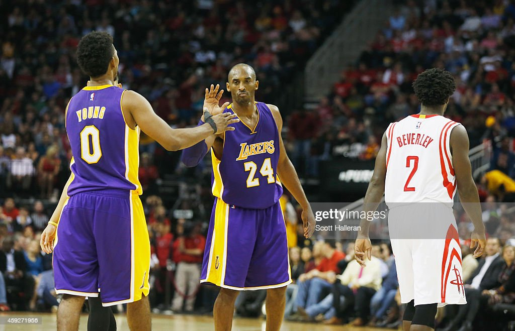 Kobe Bryant #24 of the Los Angeles Lakers celebrates a play with Nick Young #0 as Patrick Beverley #2 of the Houston Rockets walks away during their game at the Toyota Center on November 19, 2014 in Houston, Texas.
