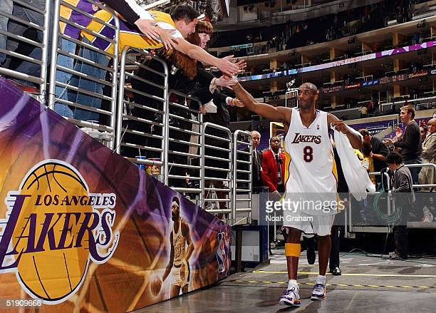 Kobe Bryant of the Los Angeles Lakers celebrates with fans while returning to the locker room after a win against the Denver Nuggets on January 2...