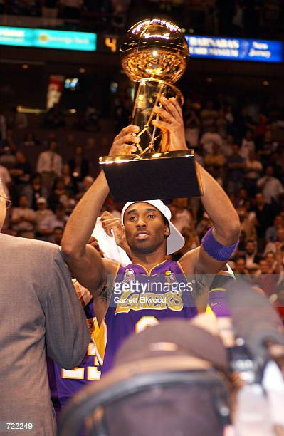 Kobe Bryant of the Los Angeles Lakers celebrates with the NBA Championship Trophy after winning the 2002 NBA Championship against the New Jersey Nets...