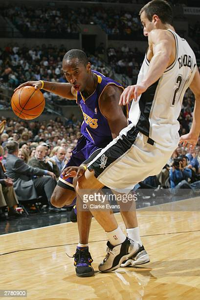 Kobe Bryant of the Los Angeles Lakers drives against Emanuel Ginobili of the San Antonio Spurs on December 3 2003 at the SBC Center in San Antonio...