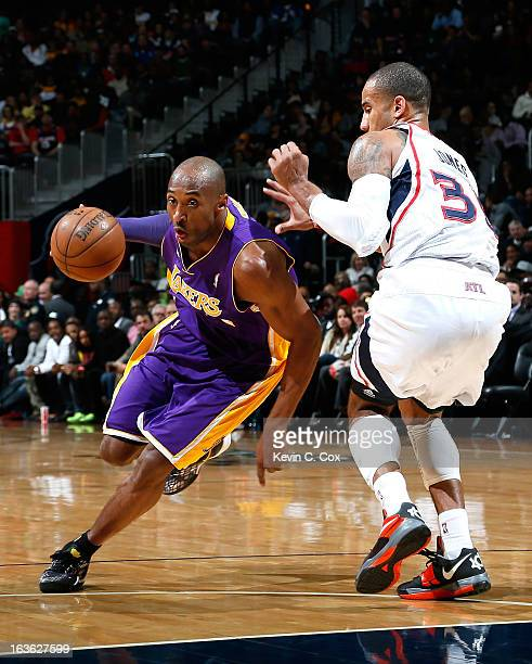 Kobe Bryant of the Los Angeles Lakers drives around Dahntay Jones of the Atlanta Hawks at Philips Arena on March 13 2013 in Atlanta Georgia NOTE TO...