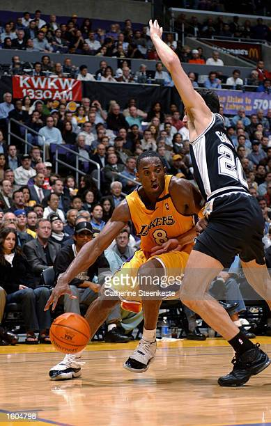 Kobe Bryant of the Los Angeles Lakers drives around Emanuel Ginobili of the San Antonio Spurs during the NBA season opener at Staples Center on...