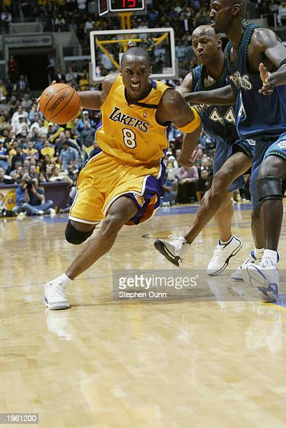 Kobe Bryant of the Los Angeles Lakers drives around Kevin Garnett and Anthony Peeler of the Minnesota Timberwolves in Game three of the Western...