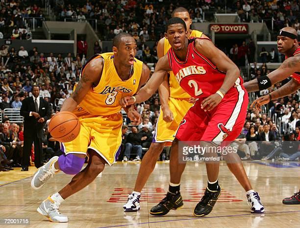 Kobe Bryant of the Los Angeles Lakers drives by Joe Johnson of the Atlanta Hawks on February 15, 2006 at Staples Center in Los Angeles, California....