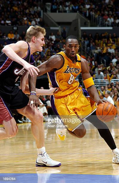 Kobe Bryant of the Los Angeles Lakers drives past Andrei Kirilenko of the Utah Jazz during a game at Staples Center on December 8, 2002 in Los...