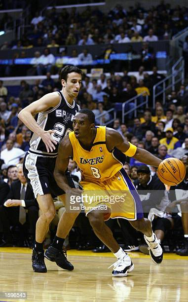 Kobe Bryant of the Los Angeles Lakers drives past Emanuel Ginobili of the San Antonio Spurs during the game at Staples Center on October 29 2002 in...