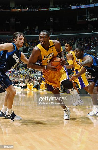 Kobe Bryant of the Los Angeles Lakers drives past Steve Nash of the Dallas Mavericks during the NBA game at Staples Center on December 6, 2002 in Los...