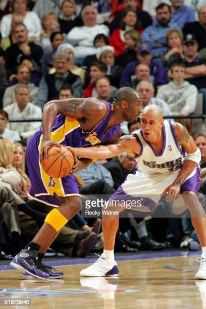 Kobe Bryant of the Los Angeles Lakers drives the ball against Doug Christie of the Sacramento Kings during the game on December 16 at Arco Arena in...