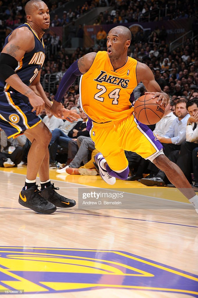 Kobe Bryant #24 of the Los Angeles Lakers drives to the basket against David West #21 of the Indiana Pacers at Staples Center on November 27, 2012 in Los Angeles, California.