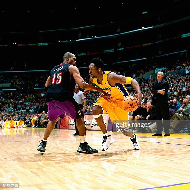 Kobe Bryant of the Los Angeles Lakers drives to the basket against Vince Carter of the Toronto Raptors during an NBA game at the Staples Center circa...