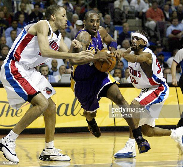 Kobe Bryant of the Los Angeles Lakers drives to the basket between Tayshaun Prince and Richard Hamilton of the Detroit Pistons during the first half...