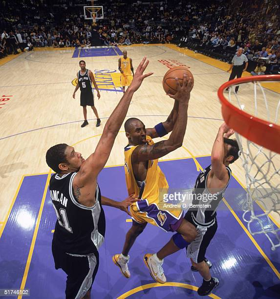 Kobe Bryant of the Los Angeles Lakers drives to the basket between Tim Duncan and Emanuel Ginobili of the San Antonio Spurs during a game at Staples...