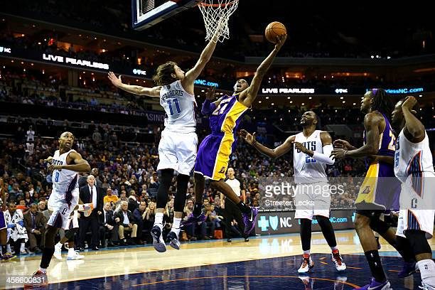 Kobe Bryant of the Los Angeles Lakers drives to the basket Josh McRoberts of the Charlotte Bobcats during their game at Time Warner Cable Arena on...