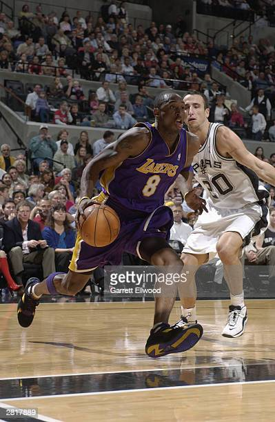 Kobe Bryant of the Los Angeles Lakers drives to the hoop past Emanuel Ginobili of the San Antonio Spurs at SBC Center on December 3 2003 in San...