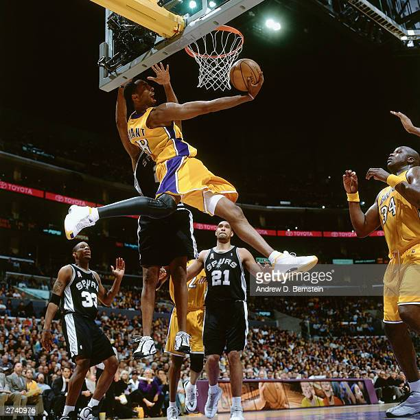 Kobe Bryant of the Los Angeles Lakers drives under the basket for a reverse dunk against the San Antonio Spurs at the Staples Center circa 2002 in...