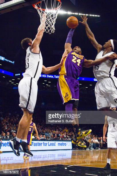 Kobe Bryant of the Los Angeles Lakers dunks against Kris Humphries and Gerald Wallace of the Brooklyn Nets on February 5 2013 at the Barclays Center...