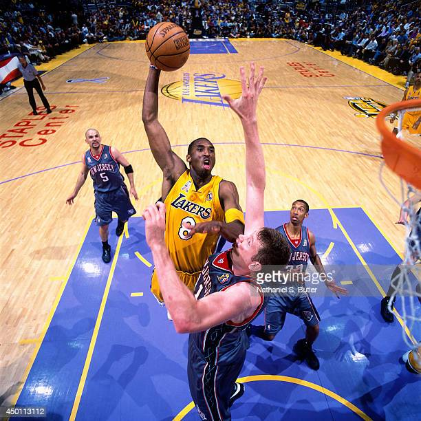 Kobe Bryant of the Los Angeles Lakers dunks against Todd MacCulloch of the New Jersey Nets during Game One of the 2002 NBA Finals on June 5 2002 at...