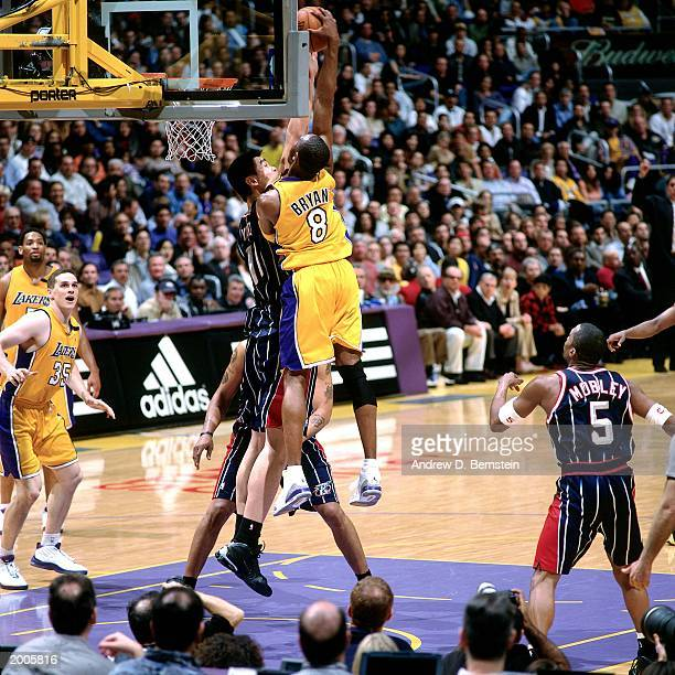 Kobe Bryant of the Los Angeles Lakers dunks against Yao Ming of the Houston Rockets during the NBA game at the Staples Center on February 18 2003 in...