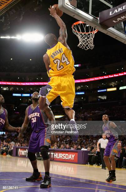 Kobe Bryant of the Los Angeles Lakers dunks as Shaquille O'Neal of the Phoenix Suns looks on during the NBA game at Staples Center on February 26...