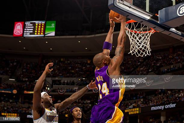 Kobe Bryant of the Los Angeles Lakers dunks the ball as Ty Lawson of the Denver Nuggets defends in Game Six of the Western Conference Quarterfinals...