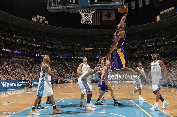 Kobe Bryant of the Los Angeles Lakers dunks the ball between Chauncey Billups, Carmelo Anthony, and Nene of the Denver Nuggets in Game Six of the...