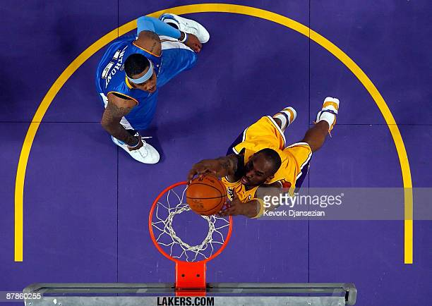 Kobe Bryant of the Los Angeles Lakers dunks the ball in front of Carmelo Anthony of the Denver Nuggets in Game One of the Western Conference Finals...