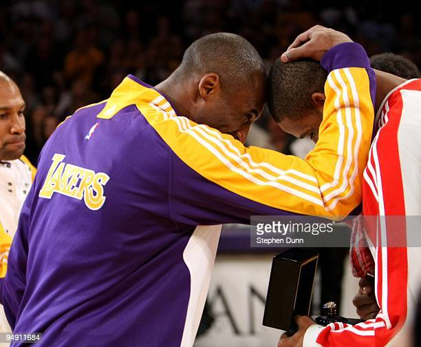 Kobe Bryant of the Los Angeles Lakers embraces Trevor Ariza of the Houston Rockets as he presents Ariza with his 20082009 championship ring he won as...