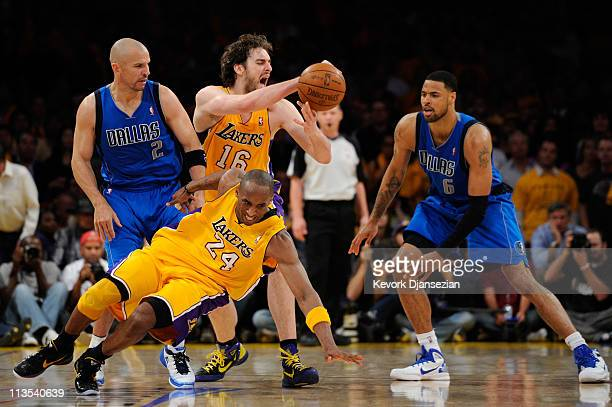Kobe Bryant of the Los Angeles Lakers falls down as Pau Gasol looses the ball in front of Jason Kidd and Tyson Chandler of the Dallas Mavericks late...