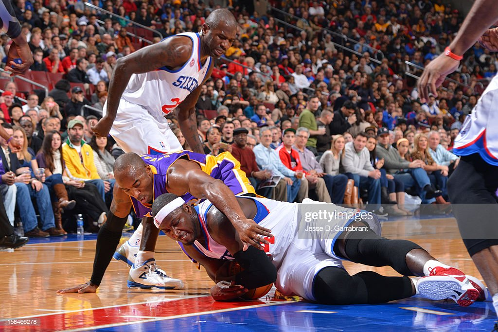 Kobe Bryant #24 of the Los Angeles Lakers fights for the loose ball against Kwame Brown #54 of the Philadelphia 76ers on December 16, 2012 at the Wells Fargo Center in Philadelphia, Pennsylvania.