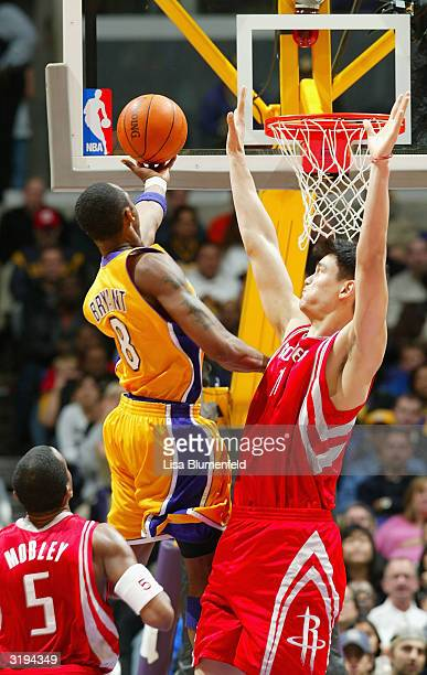 Kobe Bryant of the Los Angeles Lakers goes drives for a shot attempt over Yao Ming and Cuttino Mobley of the Houston Rockets during the game at...