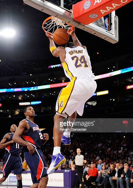Kobe Bryant of the Los Angeles Lakers goes for a reverse dunks as Joe Johnson of the Atlanta Hawks looks on during the NBA basketball game at Staples...