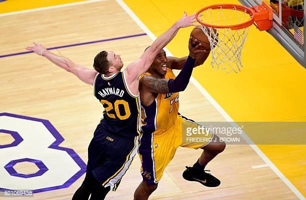 TOPSHOT Kobe Bryant of the Los Angeles Lakers goes to the hoop under pressure from Gordon Hayward of the Utah Jazz in Bryant's last game as a Laker...