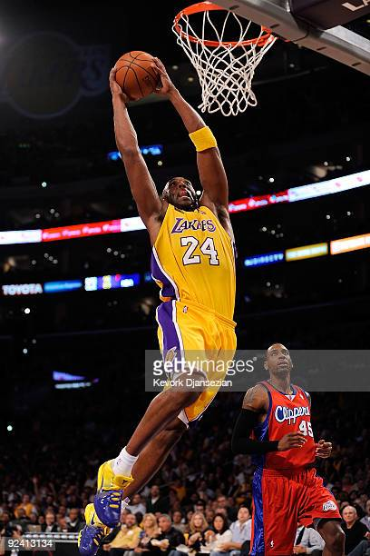 Kobe Bryant of the Los Angeles Lakers goes up for a dunk in front of Rasual Butler of the Los Angeles Clippers in the first quarter of the season...