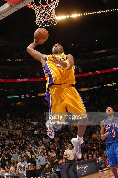 Kobe Bryant of the Los Angeles Lakers goes up for a dunk while Chris Duhon of the New York Knicks looks on at Staples Center on December 16 2008 in...