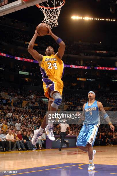 Kobe Bryant of the Los Angeles Lakers goes up for a dunk while Kenyon Martin of the Denver Nuggets looks on during their game at Staples Center on...