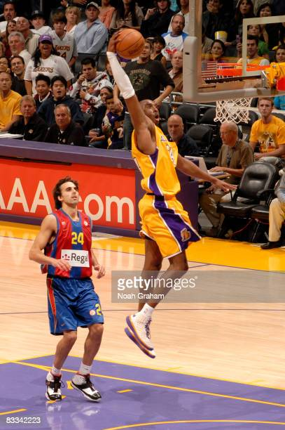 Kobe Bryant of the Los Angeles Lakers goes up for a dunk while Victor Sada of Regal FC Barcelona looks on during their game at Staples Center on...