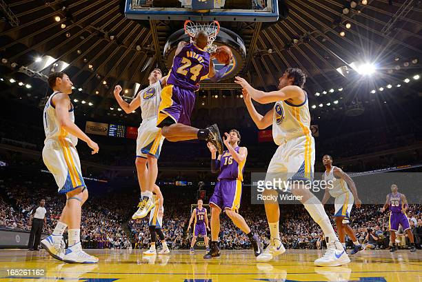 Kobe Bryant of the Los Angeles Lakers goes up for the dunk against David Lee of the Golden State Warriors on March 25 2013 at Oracle Arena in Oakland...