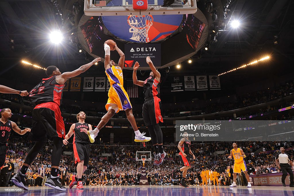 Kobe Bryant #24 of the Los Angeles Lakers goes up for the go-ahead dunk in overtime against DeMar DeRozan #10 of the Toronto Raptors at Staples Center on March 8, 2013 in Los Angeles, California.
