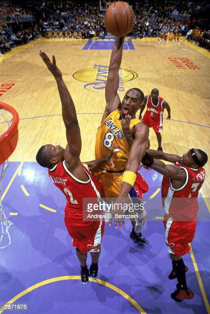 Kobe Bryant of the Los Angeles Lakers goes up to dunk the ball against Theo Ratliff and Jason Terry of the Atlanta Hawks during the NBA game at...