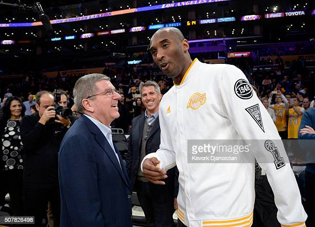 Kobe Bryant of the Los Angeles Lakers greets Thomas Bach president of the International Olympic Committee during the first half of the basketball...