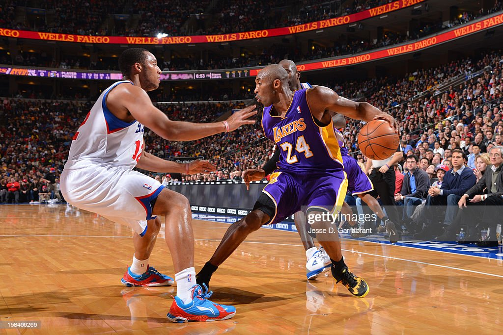 Kobe Bryant #24 of the Los Angeles Lakers handles the ball against Evan Turner #12 of the Philadelphia 76ers on December 16, 2012 at the Wells Fargo Center in Philadelphia, Pennsylvania.