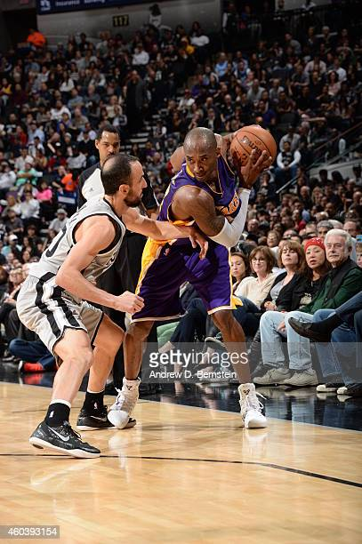 Kobe Bryant of the Los Angeles Lakers handles the ball against Manu Ginobili of the San Antonio Spurs on December 12 2014 at the ATT Center in San...