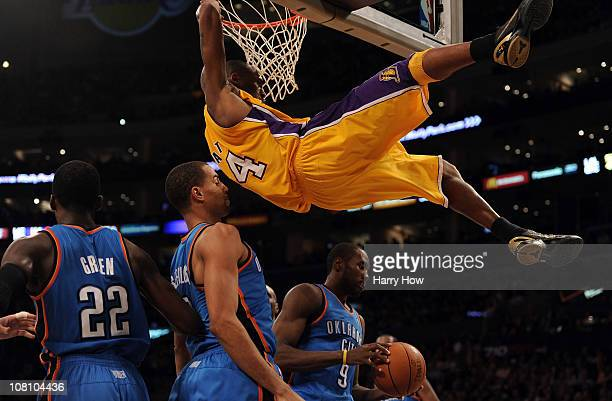 Kobe Bryant of the Los Angeles Lakers hangs on to the rim after his dunk in front of Serge IbakaThabo Sefolosha and Jeff Green of the Oklahoma City...
