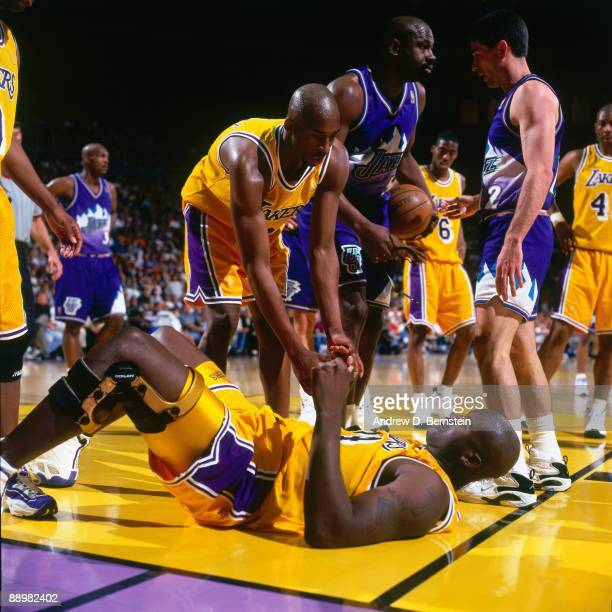 Kobe Bryant of the Los Angeles Lakers helps teammate Shaquille O'Neal up off the floor in Game Four of the Western Conference Semifinals during the...