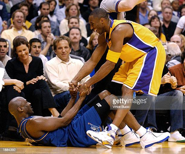 Kobe Bryant of the Los Angeles Lakers helps up Michael Jordan#23 of the Washington Wizards during the game between the Washington Wizards and the Los...