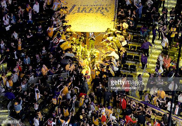 Kobe Bryant of the Los Angeles Lakers high fives fans as he walks off the court after scoring 60 points against the Utah Jazz at Staples Center on...