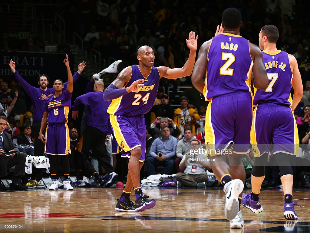 Kobe Bryant #24 of the Los Angeles Lakers high fives teammates during the game against the Washington Wizards on December 2, 2015 at Verizon Center in Washington, DC.