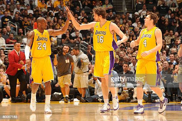 Kobe Bryant of the Los Angeles Lakers highfives teammate Pau Gasol while teammate Luke Walton looks on during their game against the Miami Heat at...