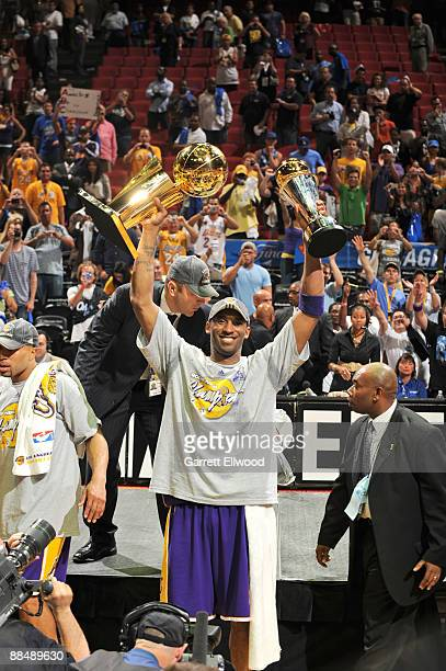 Kobe Bryant of the Los Angeles Lakers hoists the Larry O' Brien and Bill Russell MVP trophy after defeating the Orlando Magic in Game Five of the...